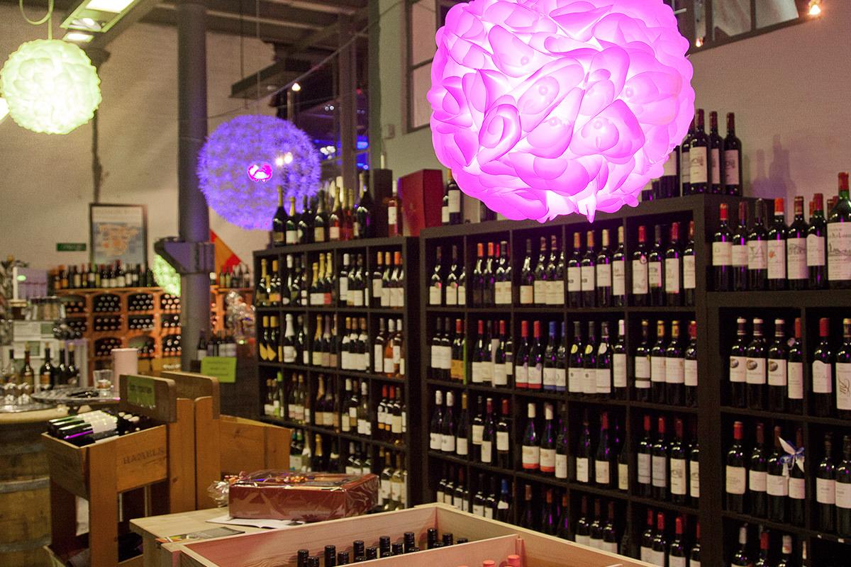 Der Shop der WeinStrecke von Innen, bei dem man auf ein großes Regal mit Weinflaschen guckt und von der Decke hängen abstrakte bunte Lampen herunter